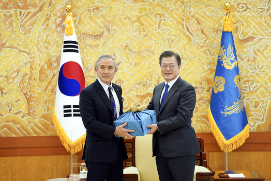 President Moon Jae-in, right, presents outgoing U.S. Ambassador to Korea Harry Harris with a farewell gift of Andong soju at the Blue House in central Seoul Tuesday. [BLUE HOUSE]