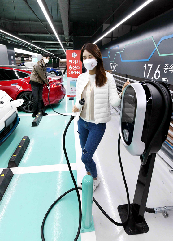 Models poses at an electric vehicle (EV) charging station located in Homeplus's Gangseo branch in western Seoul on Tuesday. Homeplus installed charging stations in the branch's parking lot for a range of EVs, including one that can charge at a rate of 17.6 kilowatts per hour. [HOMEPLUS]