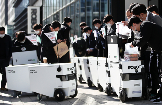 A robot developed by local robot manufacturer Robotis delivers lunch orders to office workers in Magok-dong in Gangseo District, western Seoul, on Tuesday. For a month, the company will pilot test its autonomous delivery service through a mobile app developed by IT company Vendys. [NEWS 1]