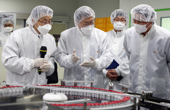 President Moon Jae-in, center, talks with SK Group Chairman Chey Tae-won, far right, Wednesday while touring a SK Bioscience factory in Andong, North Gyeongsang. SK Bioscience is in talks with Novavax to sign a technology transfer agreement involving the American drug company's Covid-19 vaccine. If signed, the vaccine will be produced locally. The Andong factory is also where Covid-19 vaccines of AstraZeneca are being produced after SK Bioscience inked a contract manufacturing organization deal with the Britain-based drug company. [YONHAP]