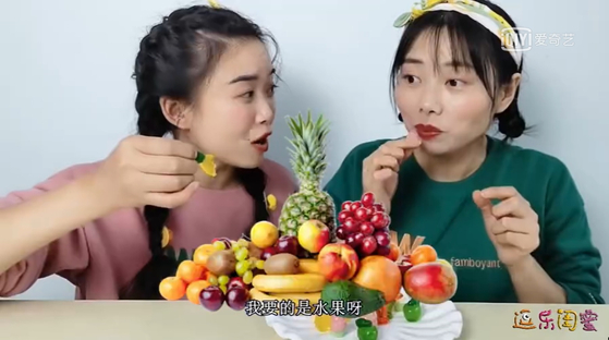 In this screen capture from iQIYI, one of the largest video streaming outlets in China, video content creators in China talk about eating gummy candy as a snack. [SCREEN CAPTURE]