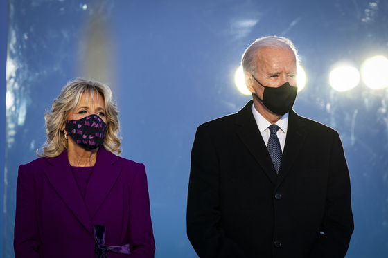 U.S. President-elect Joe Biden, right, and his wife Jill Biden, wear masks at the Lincoln Memorial Reflecting Pool during a Covid-19 memorial in Washington Tuesday on the eve of his inauguration Wednesday. [UPI/YONHAP]