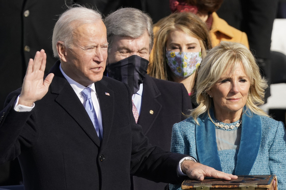 Joe Biden is sworn in as the 46th president of the United States by Chief Justice John Roberts, and his wife, Jill Biden, holds the Bible in the inauguration ceremony at the U.S. Capitol in Washington Wednesday. [UPI/YONHAP]
