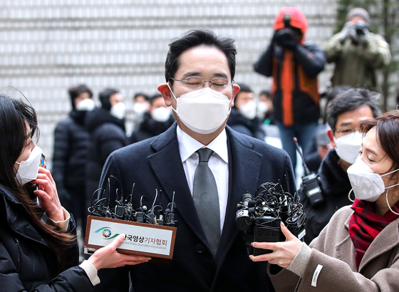 Samsung Electronics Vice Chairman Lee Jae-yong is questioned by reporters before appearing at a hearing Monday in his trial for giving bribes to former President Park Geun-hye. [WOO SANG-JO]
