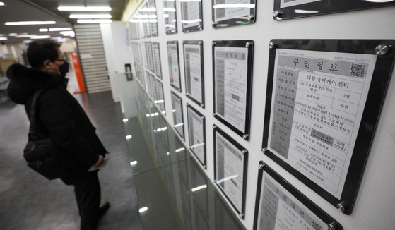 A man looks at a job bulletin board at an employment and welfare center in Mapo District, western Seoul, on Jan. 13. [NEWS1]