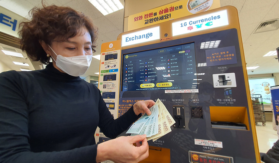 An Emart employee shows off Shinsegae Department Store gift certificates issued in exchange for foreign currency at Emart's Seongsu branch in eastern Seoul on Thursday. Emart installed kiosks capable of exchanging paper money from 16 countries and coins from 11 countries into Shinsegae gift certificates at six of its branches including the Seongsu branch and Yongsan branch in central Seoul. [YONHAP]
