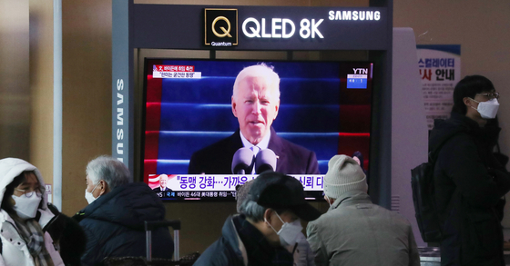 Koreans watch news on the inauguration ceremony of U.S. President Joe Biden at the Seoul Station in central Seoul Thursday. [NEWS1]