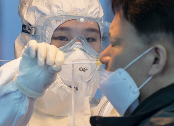 A man gets tested for the coronavirus near Seoul Station in central Seoul Friday. [YONHAP]