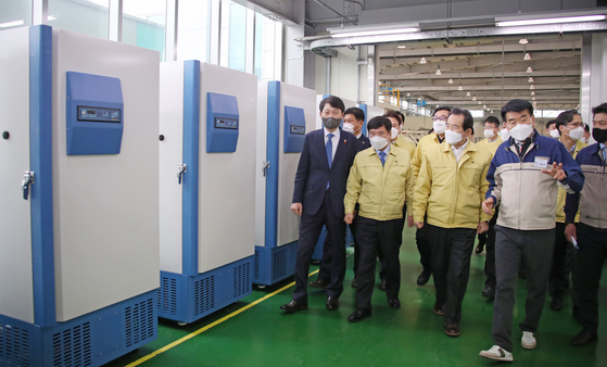 Prime Minister Chung Sye-kyun, third from left in front row, looks at ultra-cold freezers built by the Korean company Ilshin Biobase in Dongducheon, Gyeonggi on Thursday. [YONHAP]