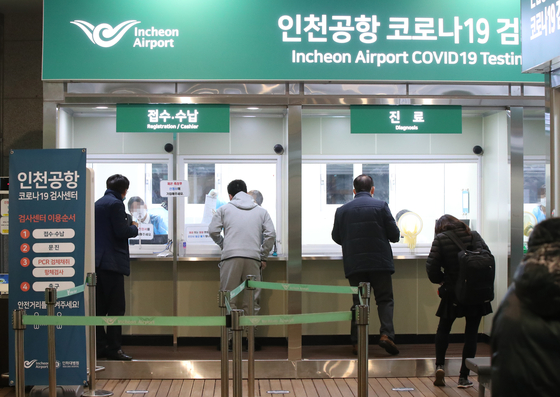 Several flight passengers stand by to take their Covid-19 test at a testing center at Incheon International Airport on Tuesday. From Tuesday, all people traveling to the United States, including U.S. citizens, have to submit a negative Covid-19 test result before boarding their planes. [YONHAP]