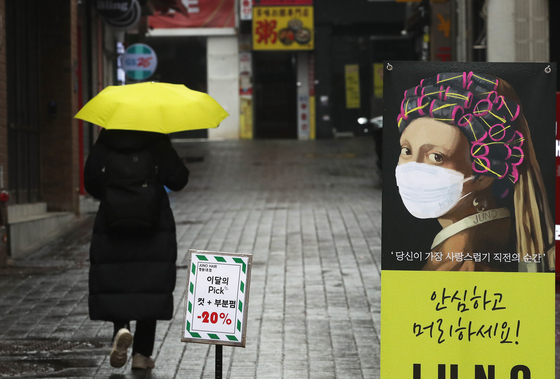 A person walks along an empty street in Myeong-dong in central Seoul on Tuesday. The coronavirus pandemic has greatly reduced household consumption, leading to a minus 1-percent growth in the country's real gross domestic product (GDP) last year, according to data by the Bank of Korea. [YONHAP]
