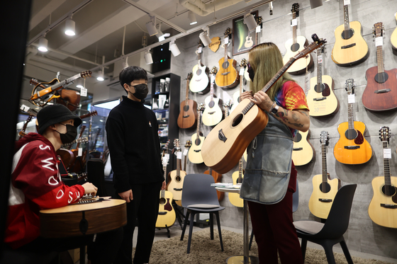 A store clerk shows a guitar to customers at an instrument shop in Seoul on Tuesday. According to Gmarket, an online market run by eBay Korea, guitar sales rose 44 percent between Dec. 25 and Jan. 24 as more people have been staying home due to the strict social distancing due to Covid-19. [YONHAP]