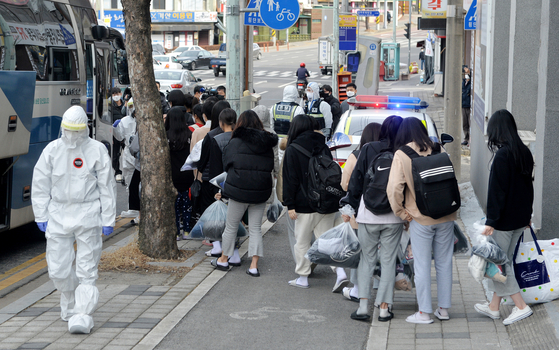 Students who were diagnosed with the coronavirus at the IEM School in Daejeon, a Christian missionary training school, board a bus Monday to be transferred to a nearby life treatment center for Covid-19 patients with mild or no symptoms. [KIM SEONG-TAE]