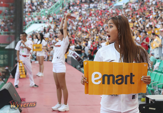 An SK Wyverns cheerleader reacts while holding an Emart sign during a game on July 13, 2019. Long before buying the club, Emart collaborated with the Wyverns on a number of promotional events. [SK WYVERNS]