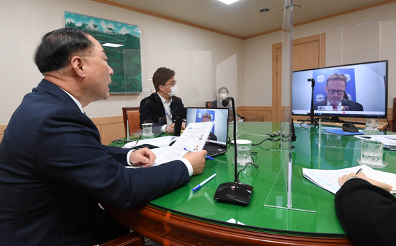 Korean Finance Minister Hong Nam-ki. left, talks with Andreas Bauer, an International Monetary Fund official in charge of Korea, in a teleconference on Thursday. [YONHAP]
