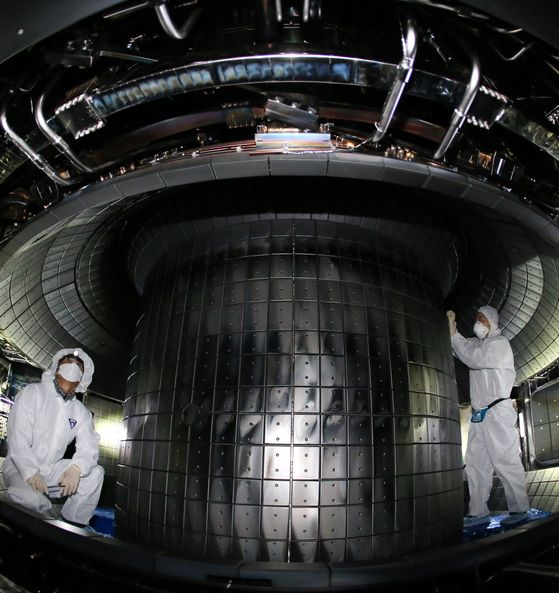 Researchers at the Korea Institute of Fusion Energy inspect the interior of the Korea Superconducting Tokamak Advanced Research (Kstar) project at the organization's headquarters in Daejeon on Wednesday. Last year, Kstar, dubbed the artificial sun, set a record by operating at 100 million degrees Celsius (180 million degrees Fahrenheit) for more than 20 seconds. The institute plans to break more records in its research into fusion energy, such as managing the temperature for 30 seconds, this year. [NEWS 1]