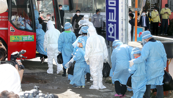 Students infected with Covid-19 at the TCS International School in Gwangsan District, Gwangju, board a bus to be transferred to a treatment center after more than 110 people were diagnosed with the virus as of Wednesday. [YONHAP]