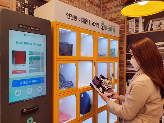 A customer looks at secondhand shoes at a secondhand exchange machine at an Emart24 store in Seoul. The convenience store is testing secondhand exchange machines developed by Parabara. The machines are located in 18 Emart24 stores across the country. With many people affected economically by Covid-19, secondhand exchanges are growing in popularity.