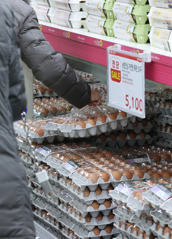 A customer picks up a carton of eggs at Hanaro Mart in Yangjae District, southern Seoul, on Thursday. Customer are limited to buying 30 eggs due to supply shortage. Egg prices have been soaring as the bird flu affects supplies. [YONHAP]
