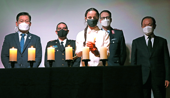 Shai Gambash, a representative of the Israeli youth in Korea, lights a candle to remember the victims of the Holocaust during the commemoration on Wednesday. Behind her, from left, are Song Young-gil, the chair of Foreign Affairs and Unification Committee of the National Assembly of Korea; Col. Yariv Ben Ezra, defense attaché of Israel in Korea; Col. Achim Neitzert, military attaché of Germany in Korea; and Hwang Woo-yeo, former deputy prime minister for social affairs and education minister. [PARK SANG-MOON]