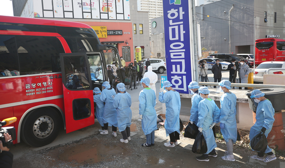 Students and faculty of the TCS International School in Gwangju who tested positive for Covid-19 are boarded onto a bus on Wednesday to be taken to a treatment center. The school is one of several unlicensed Christian missionary schools that have produced cluster infections this week due to poor observance of health regulations. [YONHAP]