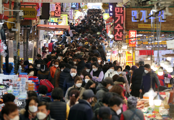 An outdoor market in Busan on Sunday is filled with customers visiting to buy products as Lunar New Year, which falls on Feb. 12 this year, is near.   [YONHAP]