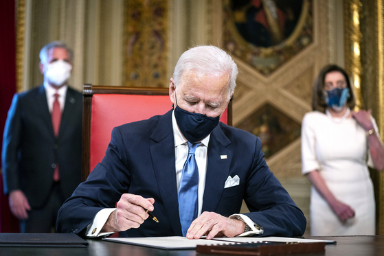 U.S. President Joe Biden signs three documents including cabinet nominations at the Capitol after his inauguration as the 46th president on Jan. 20. [UPI/YONHAP]