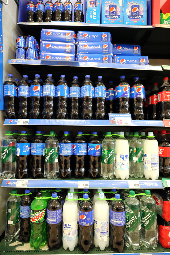 Soft drinks are displayed on the shelves of a supermarket in Seoul on Sunday. The prices of popular beverages will go up starting Monday. The price of Chilsung Cider will jump by 6.6 percent and Pepsi up 7.9 percent. [YONHAP]