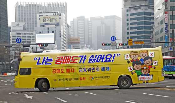 The Korea Stockholders Alliance, a group of local retail investors, operates a bus decorated with slogans promoting the short-selling ban at Gwanghwamun in central Seoul on Monday. [YONHAP]