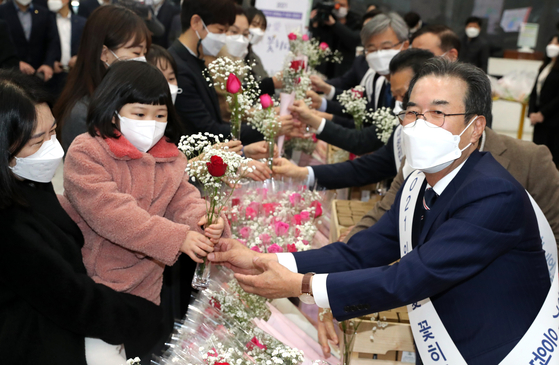 Nonghyup Chairman Lee Sung-hee, right, hands flowers to a child at the banking group's headquarters in Jung District, central Seoul on Monday. As part of efforts to help hard-hit flower farmers amid the coronavirus pandemic, Nonghyup gave away 1,000 vases filled with 2,500 flowers to employees. [YONHAP]