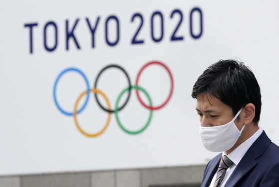 A citizen wearing a face mask passes by a Tokyo Olympics sign board near the Tokyo city hall recently. [EPA/YONHAP]