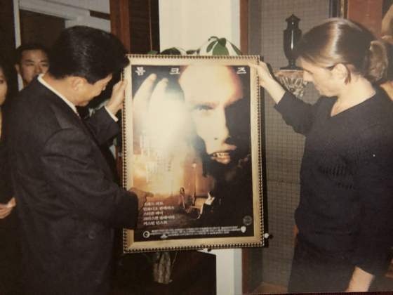 """Former general manager Park Hyo-sung of Warner Bros Korea, left, takes a look at the poster of """"The Interview with the Vampire"""" in 1994, with lead actor Tom Cruise, right, when the movie came to Korea for the first time. [PARK HYO-SUNG]"""