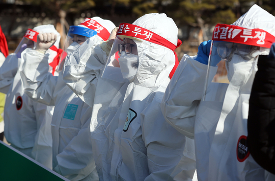 Members of the Korean Health and Medical Workers' Union hold a protest near the Blue House in central Seoul Tuesday, demanding an increase in Covid-19 medical workers and better standards and treatment. [YONHAP]
