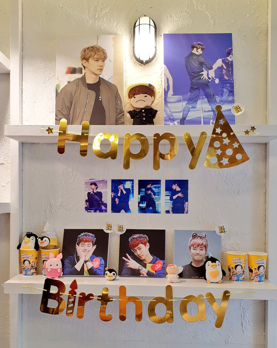 """A cafe is decorated with pictures of K-pop stars taken by avid photographers referred to as ″homma.″ The framed pictures and other merchandise such as coffee cup sleeves are later sold to the fans who visit the cafe as a part of """"birthday tours"""" to celebrate their favorite idols. [SCREEN CAPTURE]"""