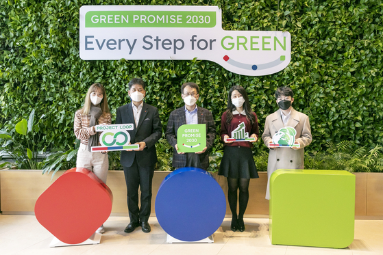 Lotte Chemical CEO and President Kim Gy-hyun, center, and company employees announce the ″Green Promise 2030,″ on Tuesday. [LOTTE CHEMICAL]