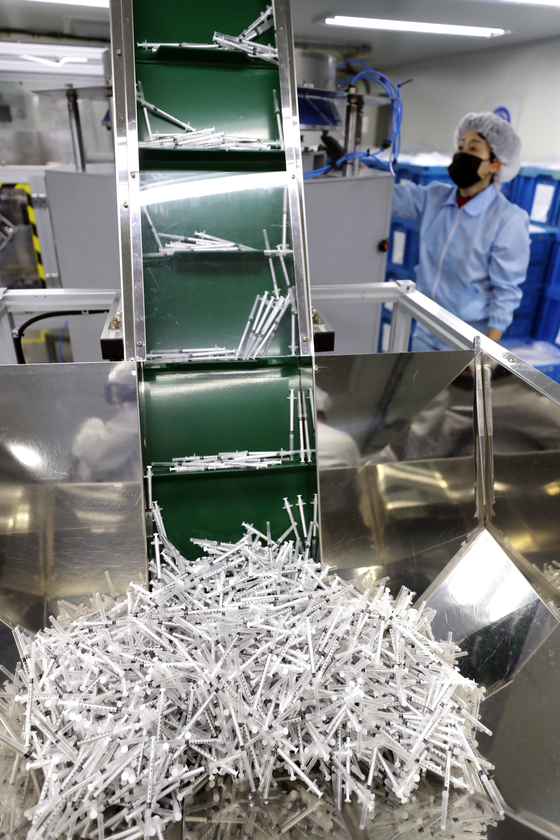 An employee at medical equipment manufacturer Shina Corporation monitors production of syringes for coronavirus vaccines in Gongju, South Chungcheong on Tuesday. The Ministry of Food and Drug Safety said Minister Kim Gang-lip visited the site and promised support for the manufacturing process and exports. [YONHAP]