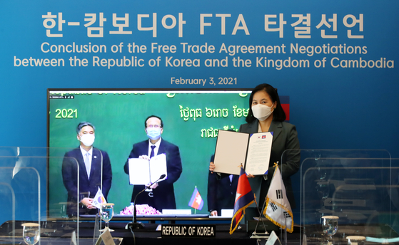 Trade Minister Yoo Myung-hee, far right, poses for a photo with Pan Sorasak, center, minister of commerce of the Royal Government of Cambodia, Wednesday during online FTA negotiations. [YONHAP]