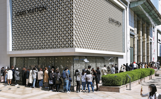 People line up outside the Lotte Department Store's main branch in Jung District, central Seoul, after news broke of price increases by French luxury fashion brand Chanel last May. [YONHAP]