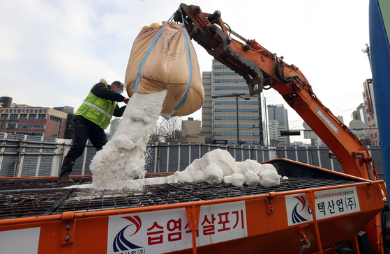 Workers unload calcium chloride on snowplow trucks in Jongno District, central Seoul, Wednesday to prepare for heavy snowfall as forecast by the weather agency. [YONHAP]