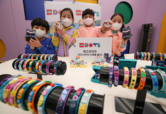 Kids pose with bracelets and ornaments made with Lego at the launching event of Lego Korea's new do-it-yourself Lego Dots range at a pop-up store at Coex in Samseong-dong, southern Seoul on Thursday. [YONHAP]