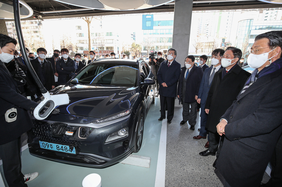 Eun Sung-soo, chairman of the Financial Services Commission, right, Sung Yun-mo, minister of trade, industry and energy, second from right, and other industry officials and executives watch a demonstration of Hyundai Motor's Kona Electric's rapid charging technology at Hyundai EV (electric vehicle) Station in Gangdong District, eastern Seoul, on Thursday. On the same day, Hyundai Motor Group in partnership with government bodies, financial institutions and private entities agreed to form a 200-billion-won ($178.8 million) worth fund within 2021 to invest in domestic auto parts companies to foster the country's future mobility business. [YONHAP]