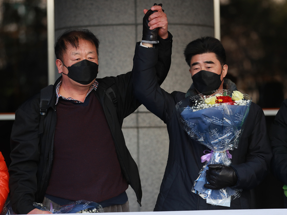 Choi In-cheol, right, and Jang Dong-ik hold hands in the air together after the Busan High Court on Thursday acquitted them in a retrial of the 31-year-old Nakdong River murder case. The pair served 21 years in prison but argued their confessions were extracted through torture by the police. [YONHAP]