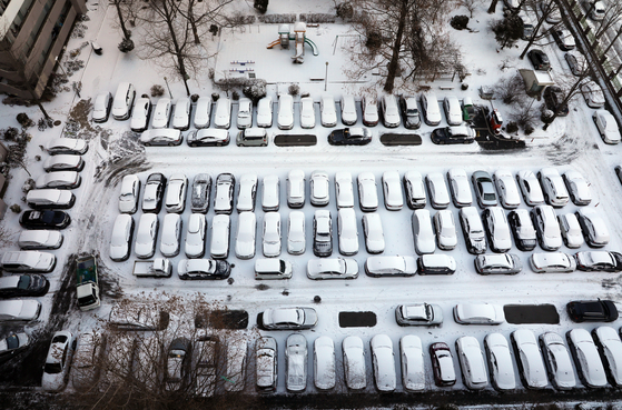Cars remain in an outdoor parking lot at an apartment complex in Seoul Thursday morning as residents eschew driving in favor of public transport after overnight snowfall. [YONHAP]