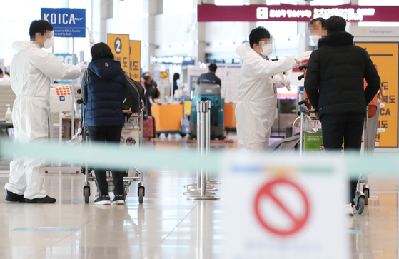 Health officials place stickers on travelers from abroad at the Incheon International Airport Terminal 1 Thursday afternoon amid concerns over the spread of coronavirus variants from overseas. [YONHAP]