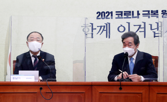 Finance Minister Hong Nam-ki, left, and Democratic Party leader Lee Nak-yon at the National Assembly on Jan. 20. [YONHAP]