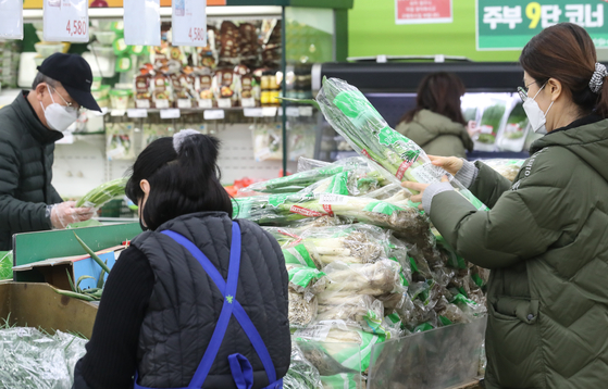 Consumers shop in the produce section at a local mart in Seoul on Friday. The price of food used in Lunar New Year celebrations have been rising rapidly, including eggs. [YONHAP]