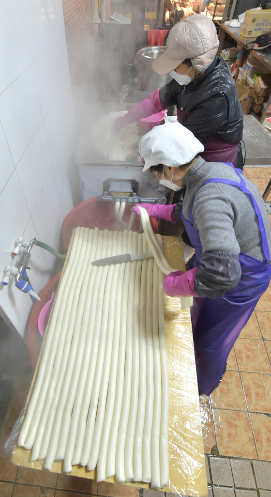 Owners of a tteok (sticky rice cake) shop in the Dongmun Traditional Market in Jeju are making bar-shaped rice cakes on Monday, three days before Lunar New Year. [YONHAP]