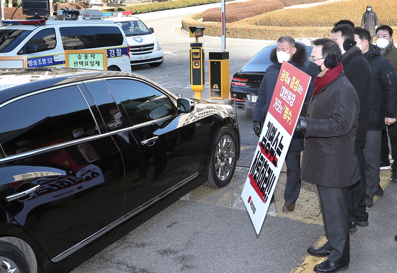 Floor leader Joo Ho-young of the People Power Party holds a sign demanding the resignation of Chief Justice Kim at the entrance of the Supreme Court as the justice's car enters the compound. [YONHAP]