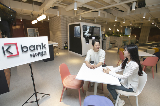 Workers talk in the new K bank office in Euljiro, central Seoul. The new office has been designed with top notch digital equipment to improve working environment, the internet-only bank said Tuesday. In the lounge, a coffee-making robot has been installed. [KBANK]