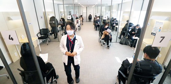 Medical workers and participants of a mock drill are on standby, at the National Medical Center in central Seoul on Tuesday, to run through the administering of Covid-19 vaccines as the government announced inoculations could begin on Feb. 26. [JOINT PRESS CORPS]